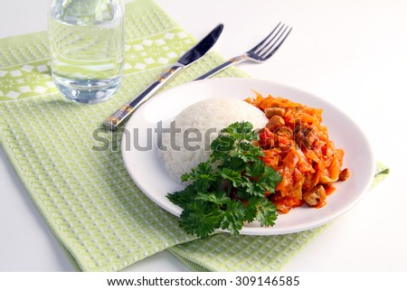 Still Life: roast pork with cabbage, white rice and a bunch of parsley on a white dish, on  a green towel, water glass and cutlery on a white background