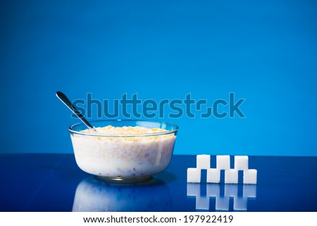 Still life showing amount of sugar in a bowl of cereals and fresh milk - stock photo