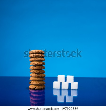Still life showing amount of sugar in a stack of chocolate chip cookies - stock photo