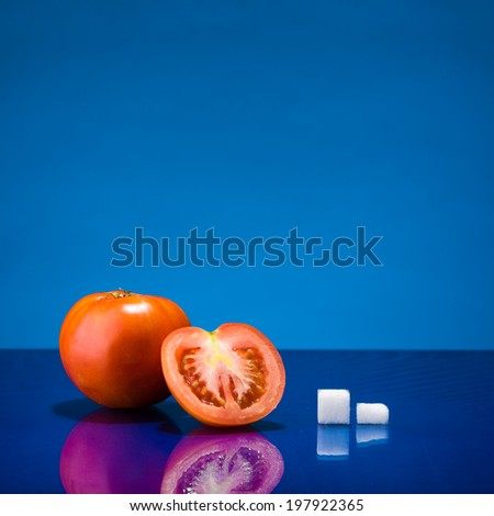 Still life showing amount of sugar in one and a half tomato - stock photo