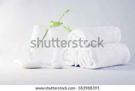 Still life spa setting with towels and young orchid flower in glass - stock photo