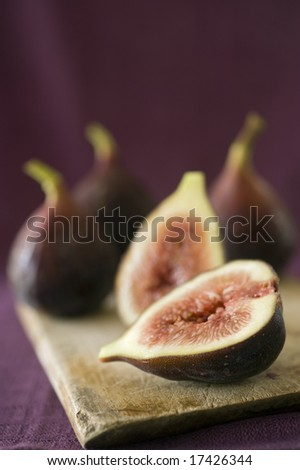 still life three whole figs and one sliced on a wooden cutting board - stock photo