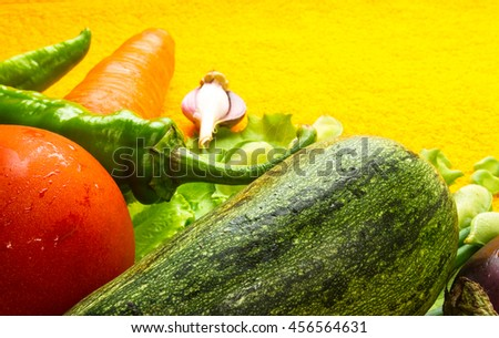 still life - tomato, carrots, onion, lettuce, cucumber, cilantro, eggplant and peppers on bright yellow background - stock photo