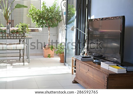 Still life view of a home living room with a flat screen TV, with a small terrace garden outdoors area, indoors and outdoors. Home entertainment technology, empty space, aspirational lifestyle. - stock photo