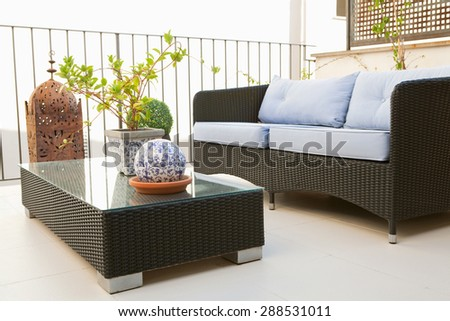 Still life view of a home outdoors terrace balcony relaxing and lounging area with wicker coffee table and sofa, in an elegant house, exterior. Summer home living, empty space, aspirational lifestyle. - stock photo