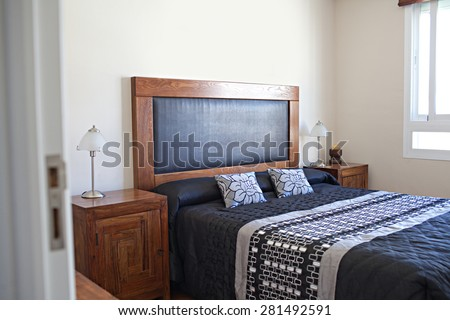 Still life view of an apartment masculine bedroom with wooden furniture in a bright home interior. Cozy and comfortable bed room view with a bright window, house interior and home living detail. - stock photo