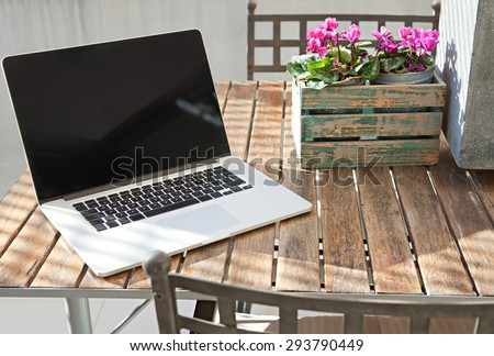 Still life view of open laptop computer on a terrace patio wooden table with decorative flower pot in home exterior area, outdoors. Technology at home and working from home environment with no people. - stock photo