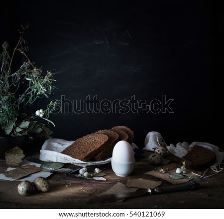 still life. vintage. a simple country breakfast on  wooden table. bread, eggs. black background