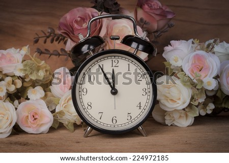still life, vintage alarm clock with flowers on wooden table - stock photo