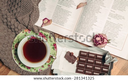 Still life. Warm, knitted sweater, a cup of hot tea, chocolate, a book on wooden background. top view - stock photo