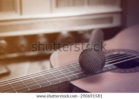 Still life whit Microphone and classic guitar on vintage Radio  background,vintage style, Beautiful light made with color filters - stock photo