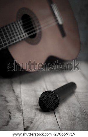 Still life whit Microphone and classic guitar waiting on wooden floor, vintage style - stock photo