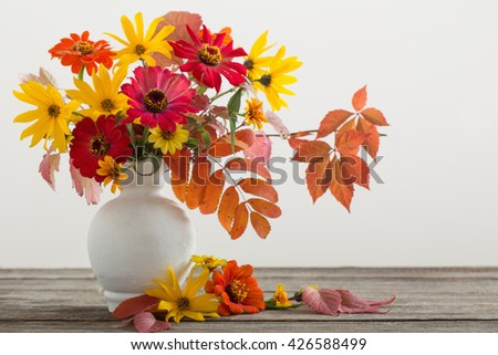 Still life with a autumn flowers and leaves - stock photo