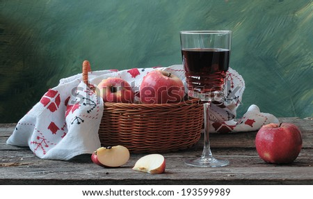 Still-life with a basket filled juicy ripe fruit and fragrant red wine in a graceful glass - stock photo