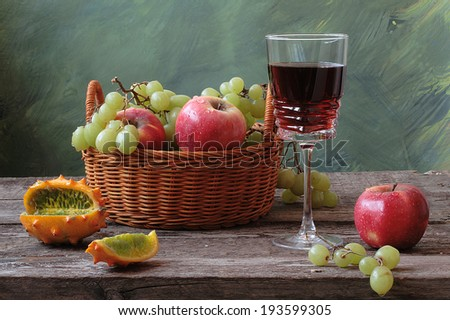 Still-life with a basket filled juicy ripe fruit and fragrant red wine in a graceful glass and the Antilles cucumber - stock photo
