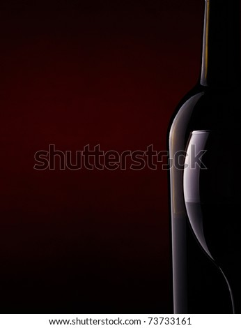 Still life with a bottle and a goblet of red wine on a dark background. - stock photo