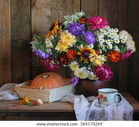 Still life with a bouquet of autumn flowers and pumpkin in a basket against boards. - stock photo