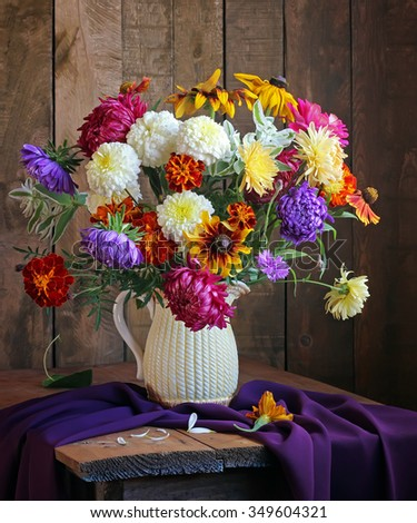 Still life with a bouquet of autumn flowers in a jug against from boards. - stock photo