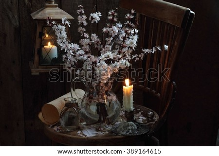 still life with a bouquet of flowering branches of apricot and candle