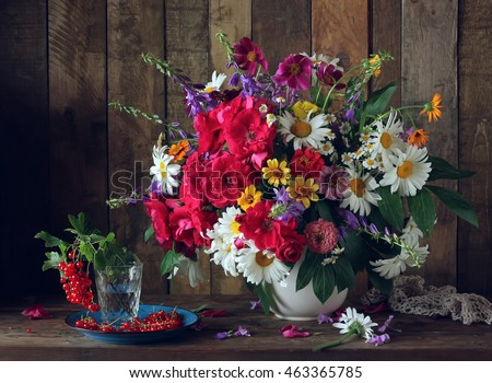 Still life with a bouquet of garden flowers in a white pitcher and red currant, rustic style.