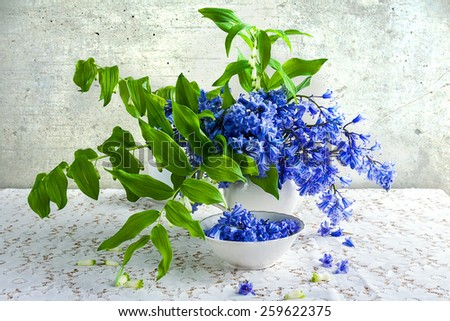 Still life with a bouquet of polygonatum, blue tones and white crockery - stock photo