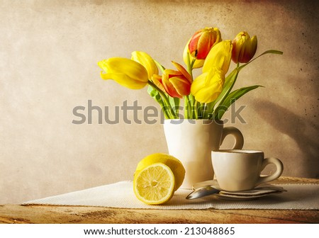 Still life with a bouquet of yellow tulips and cup of tea - stock photo