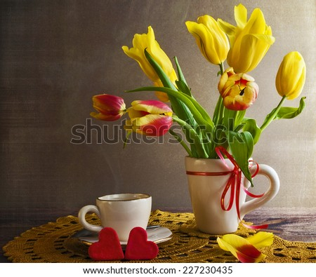 Still life with a bouquet of yellow tulips and hearts - stock photo
