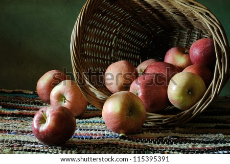 Still life with a bunch of apples and a basket - stock photo