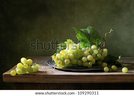 Still life with a bunch of green grapes - stock photo