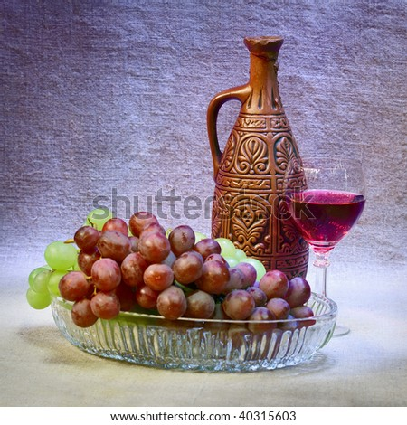 Still-life with a clay bottle, grapes and a glass - stock photo