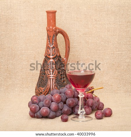 Still-life with a clay bottle, grapes and a glass on a canvas background - stock photo