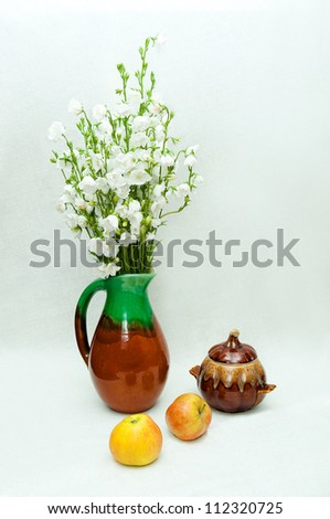 still life with a clay vase of bells and apples - stock photo