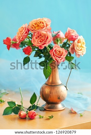 Still life with a fresh roses in a vintage jug .(blue background) - stock photo