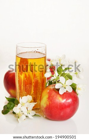 Still life with a glass of fresh juice and ripe red apples - stock photo