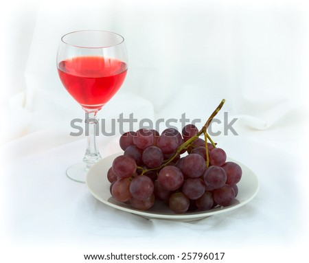 Still-life with a glass of red wine and grapes on a white background - stock photo