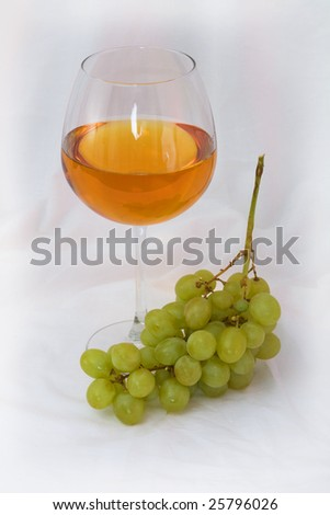 Still-life with a glass of wine and grapes on a white background - stock photo