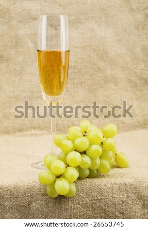 Still-life with a glass of wine and grapes on sacking background - stock photo