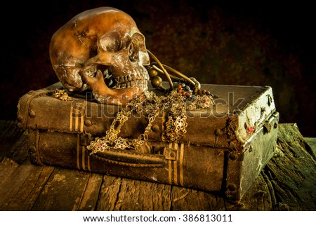Still life with a human skull with old treasure chest and gold, diamond and jewelry