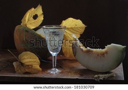 Still-life with a melon both yellow autumn leaves and a graceful glass, a fragrant ripe sweet melon and autumn yellow bright leaves and water in a graceful beautiful wine glass - stock photo