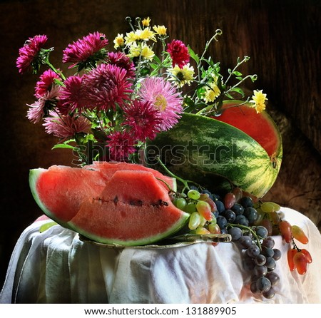 Still-life with a red ripe juicy water-melon, sweet grapes and a bright bouquet of asters - stock photo