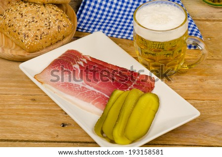 Still life with a smoked ham snack served with beer