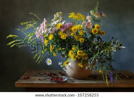 Still life with a voluptuous bunch of field flowers and red currants - stock photo