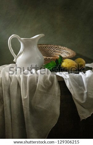 Still life with a white jar and two lemons - stock photo