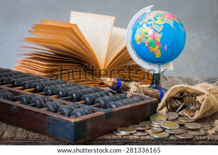 still life with abacus, coin and old book on a wooden table, financial concept