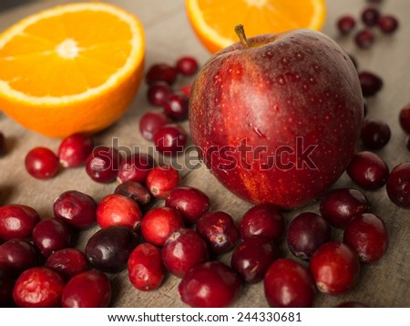 Still life with an apple, cranberries, and an orange - stock photo