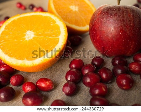 Still life with an orange, cranberries, and an apple - stock photo