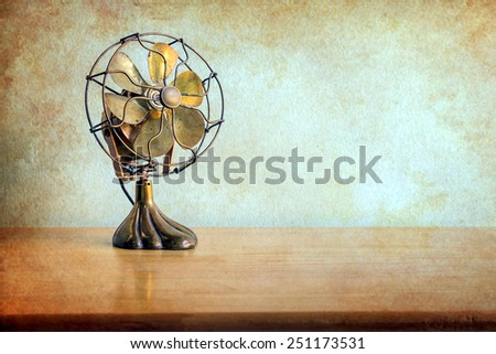 still life with antique fan on wooden table over grunge background - stock photo