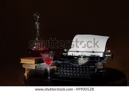 still life with antique typewriter wine carafe and old books