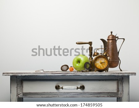 Still life with apple alarm clock and tea on the table - stock photo