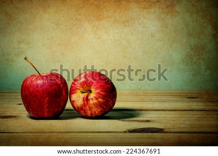 still life with apple on wooden table over grunge background - stock photo